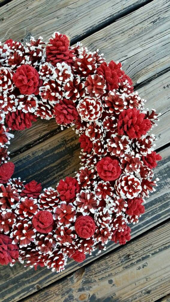 Hundreds of pine cones were used to create this elegant Christmas wreath. Two types of pine cones were used... red painted pine cones dipped in white and red flocked pine cones. This is perfect for a kitchen, dining room, or living room! It can also be displayed on your front door.