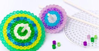 Mit dieser schönen Idee aus Bügelperlen hat man jede Menge Spaß.    Du brauchst: Bügelperlen Runde Bügelperlenplatte Bügelpapier oder Backpapier Stiele für Cakepops   So geht's: Legt einen bunten Kreis aus Bügelperlen auf die Platte und lasst dabei ein Loch in der Mitte. Bei bunten Farben sieht es besonders schön aus, wenn [...]