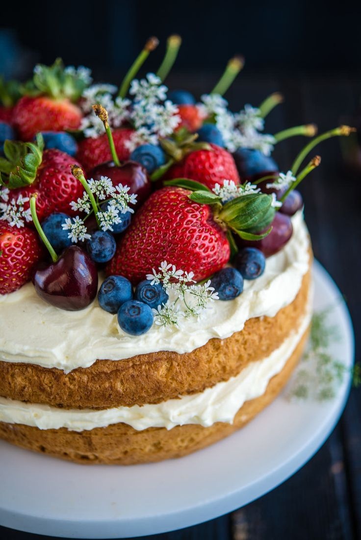 Wow, beautifull! Sponge Cake with Berries and Cherries.  Decorated with strawberries, dark cherries, blueberries and the white flowers of a coriander plant.