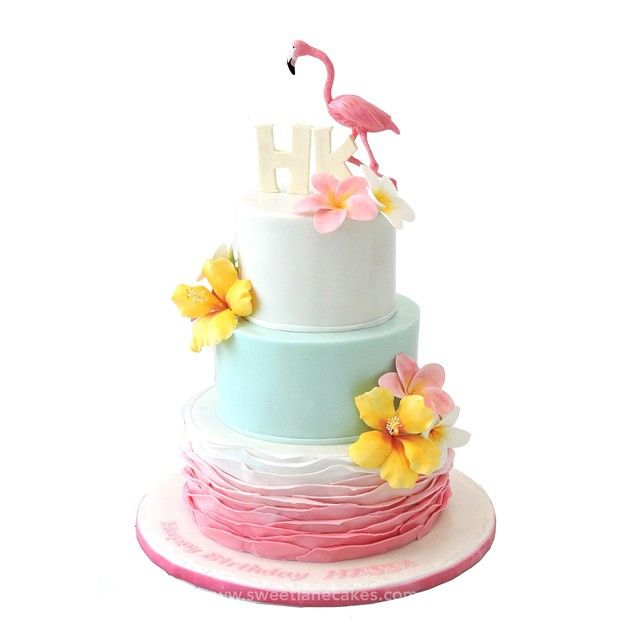 We love this all-edible tropical themed cake in pretty colors adorned with perfectly formed hibiscus and plumeria sugar flowers and cute flamingo sugar topper