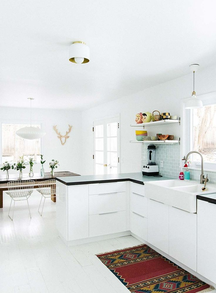 white kitchen with white floors, subtle mint finishes, and quirky accessories