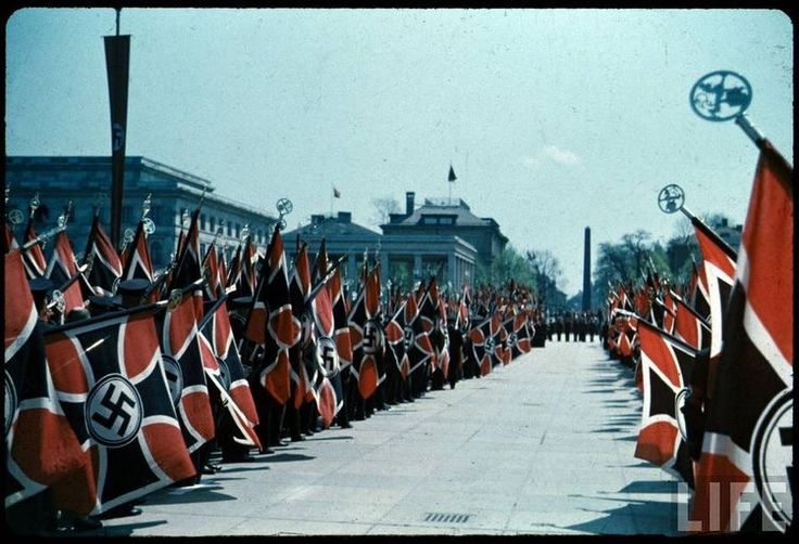 German Wehrmacht partake in a national military parade with German Wehrmacht ceremonial flags as far as the eye can see. Summer, 1938.