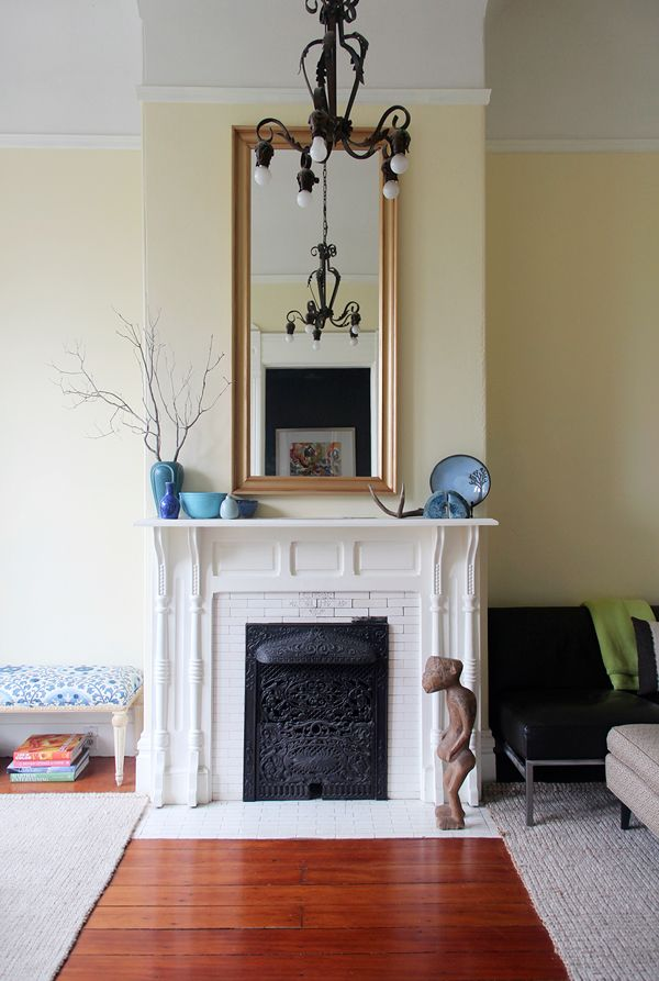 The blue pottery arrangement works really well with the gold mirror frame, vintage chandelier, vintage fireplace screen, and pale pale yellow walls (Benjamin Moore: Pale Moon)