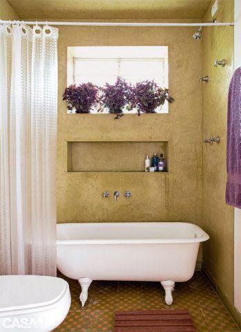 Nada de azulejos: são também de cimento queimado com pigmento as paredes do banheiro. Cavado na alvenaria, o nicho não toma espaço. Sonho da moradora, a banheira vitorania teve de ser instalada na área do boxe, sob o chuveiro. Ladrilho hidráulico da Dalle Piagge.