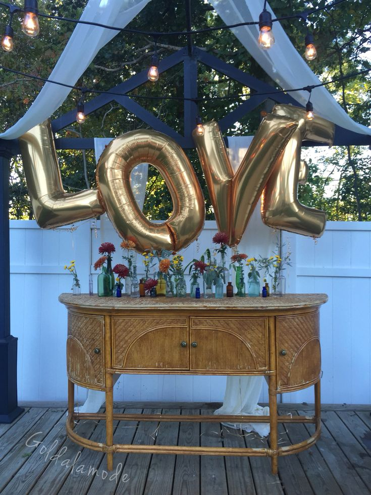 Gold letter balloons, antique bottles, and antique furniture for a DIY backyard engagement party!