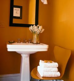 "The powder room is bathed in a blaze of orange-yellow. ""Small baths or halls can be great spots for strong color: they allow you to experience the shade in small doses"