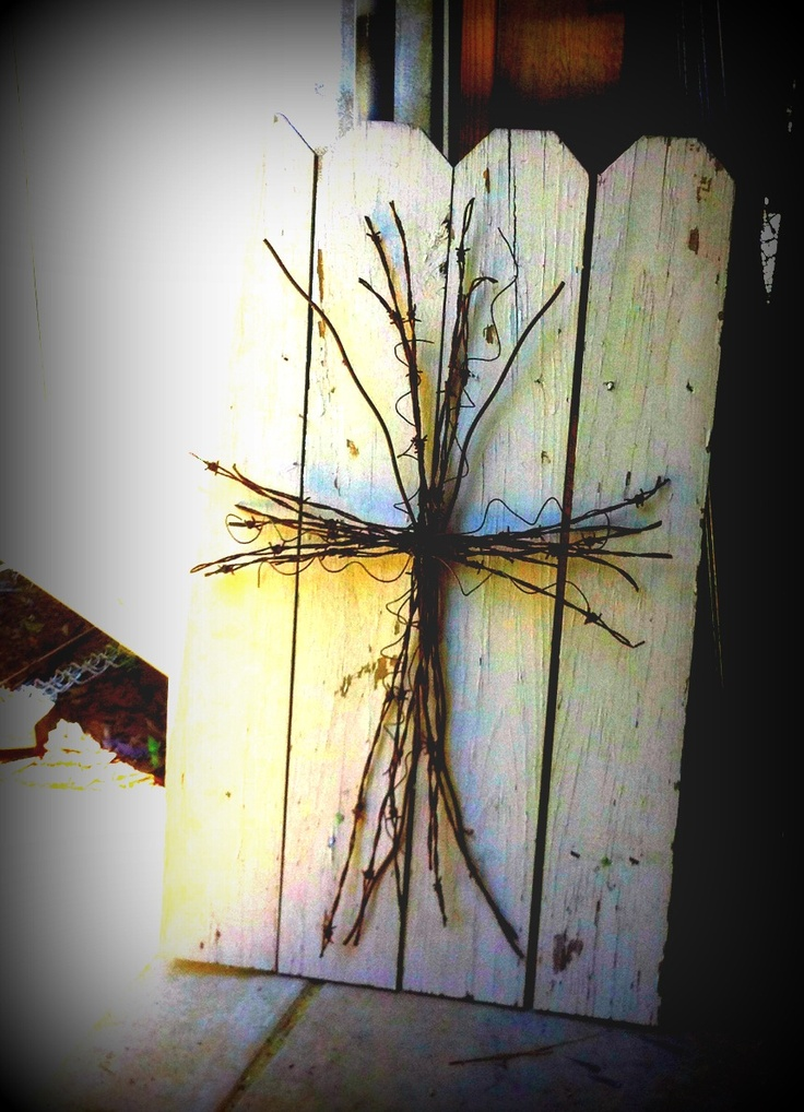 Rusted Barbed Wire Cross on an Old Weathered Wood Fence piece