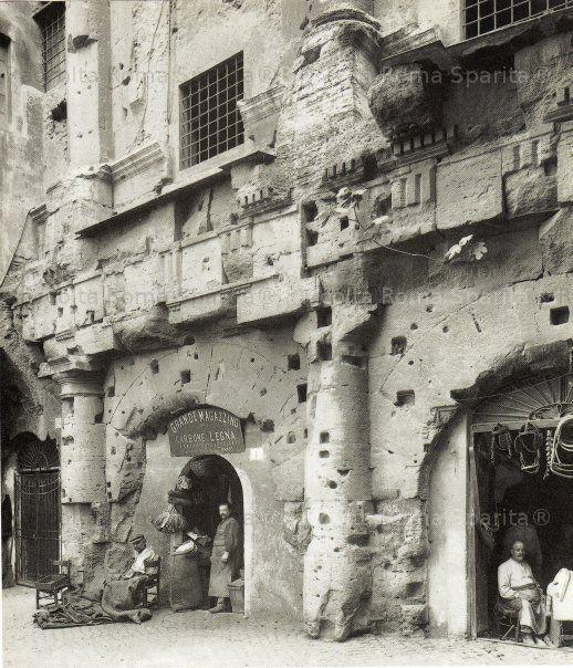 Teatro Marcello con le botteghe ricavate nei fornici del teatro. Le botteghe saranno smantellate tra il 1926 e il 1932. Anno: 1875 – 1932