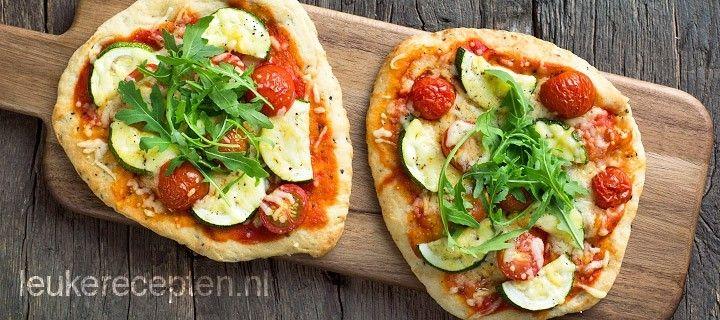 Snelle pizza van naanbrood met tomatensaus, groenten en kaas