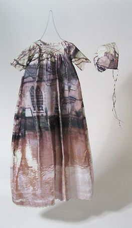 Baptism by Shelly Goldsmith - Heat transfer printing, stitch deconstruction of reclaimed christening dress and bonnet. Photographic imagery of UK flood devastation