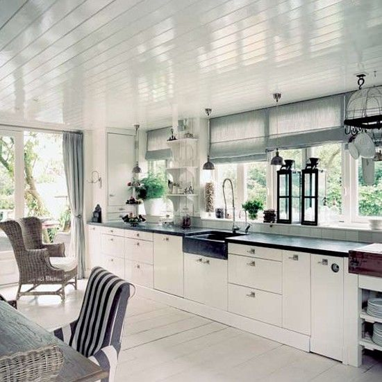 simple white kitchen... floors, ceiling lights, casual stripes on chairs, black work surfaces... not keen on cabinets