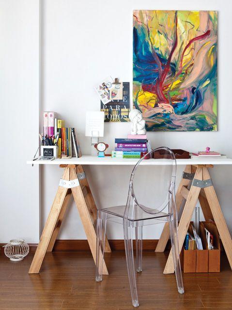 Escritorio súper compacto armado con caballetes y placa blanca, que recibe los toques de estilo con silla tipo Louis Ghost de acrílico transparente y pintura.