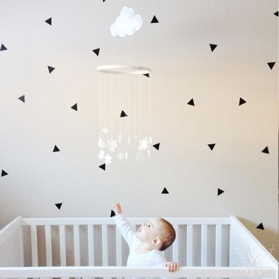 Small black triangle wall stickers on white wall behind mother kissing her baby on the cheek and white baby crib.