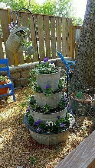 galvanized pots and watering can recycled into planters
