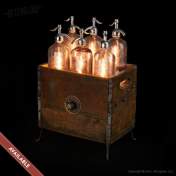 """Six mismatched seltzer bottles are propped up and illuminated from within. With a 1.5""""dia hole cored through their bases, each bottle acts as a 'shade.' Simply slip on/off to change the bulb. Operated by a rotary dimmer disguised as a drawer pull (front center of box).  $1400.00"""