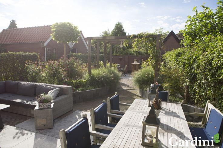 De zachte kleur hout van de tuinsets op de beide terrassen past perfect bij de houtkleur van de bogen, waardoor eenheid in de tuin wordt gecreëerd.