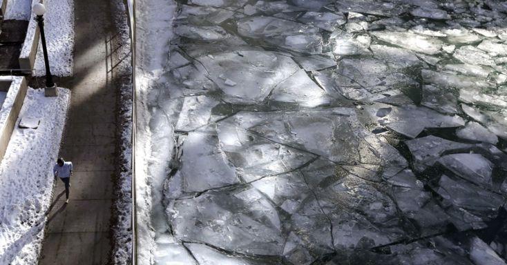 Pessoa caminha à beira do rio Chicago, que atravessa o centro da cidade de Chicago, no estado de Illinois, USA, congelado em razão das baixas temperaturas que atingem os USA em janeiro de 2018.  Fotografia: Nam Y. Huh / AP Photo.  https://noticias.uol.com.br/album/2018/01/03/onda-de-frio-nos-eua.htm#fotoNav=22