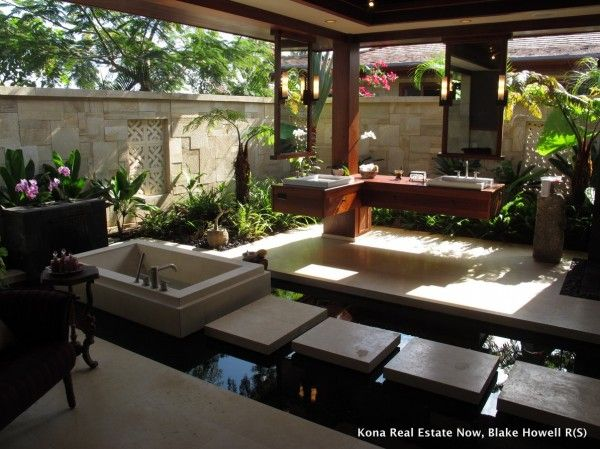 In this Hawaiian bathroom, the user is forced to slow down, stepping carefully along a pathway across a modernist pond to reach the deep soaking tub. From the lower point of view in the tub, there's still plenty to see, as the sink and counter have been cantilevered to float, so as not to cut off the view.