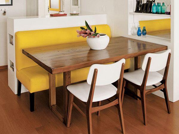 mesa de jantar, um banco colorido e duas cadeiras brancas