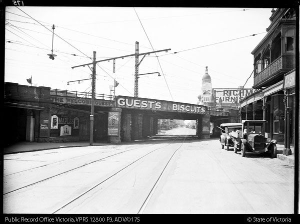 RAILWAY BRIDGE OVER SWAN STREET RICHMOND LOOKING EAST ADVERTISING FOR GUEST'S BISCUITS, ANSEL TABLETS, MAPLES, CITREON CARD. CHEVROLET CAR PARKED IN STREET - Public Record Office Victoria