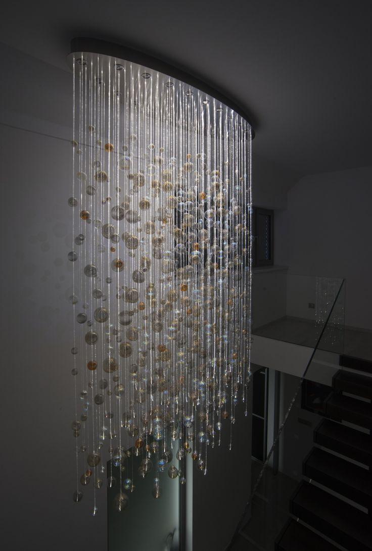 Modern chandelier made of hand blown glass hanging on sparkling fiber optics. Night mode.