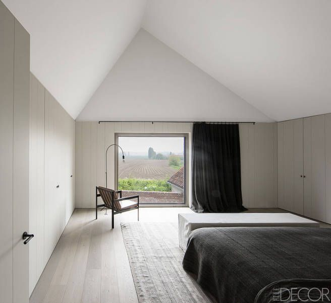 Inside A Streamlined Belgian Farmhouse - The master bedroom looks out onto farm fields. The cabinetry is custom made, and the floor is oak.