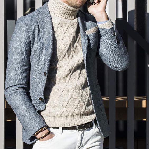 Acheter la tenue sur Lookastic: https://lookastic.fr/mode-homme/tenues/blazer-pull-a-col-roule-jean/21198   — Pull à col roulé en tricot beige  — Pochette de costume beige  — Blazer en laine gris  — Ceinture en cuir noir  — Jean blanc