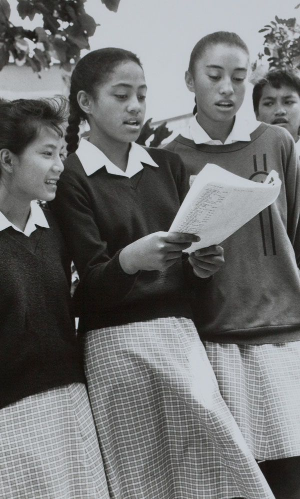 """'Carol singing instills pride', Otahuhu, 1989.  """"These three choir singers from Otahuhu Intermediate School share a song sheet while singing at the Otahuhu shopping centre last week."""" (Manukau Courier, 14 December 1989, p. 14)  Creator: Unknown Date: December 1989 Location: Otahuhu Medium: Black and white photograph , 20 x 13 cm  Manukau Research Library, Courier collection, box 38/57. Footprints 00670  Photograph reproduced by permission of Fairfax Media."""