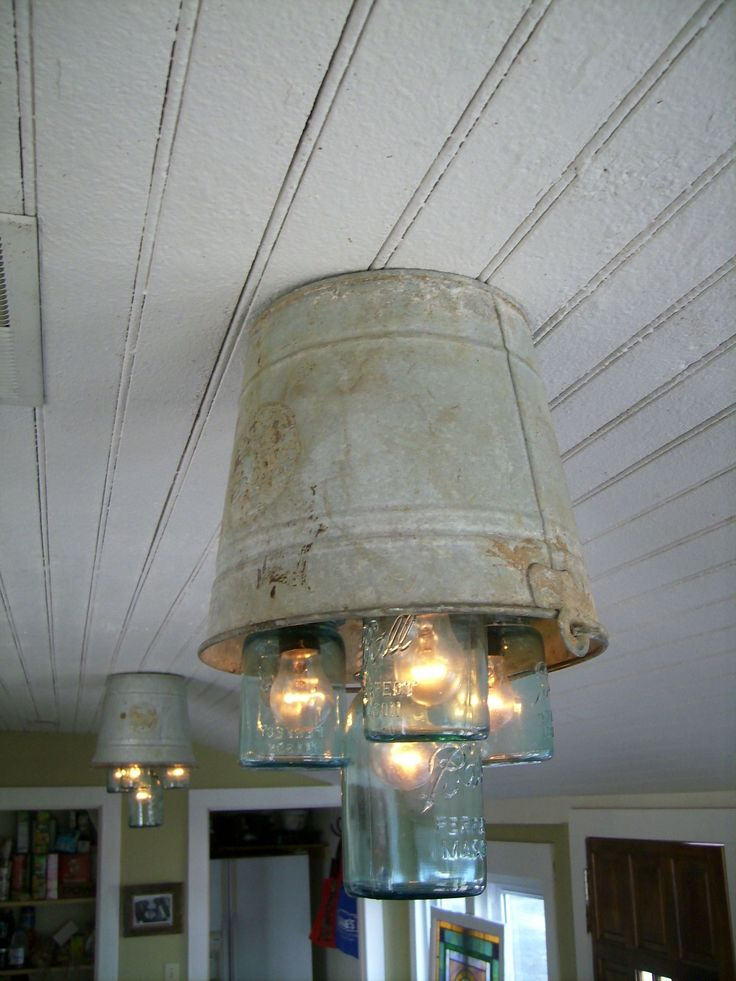 Tin bucket chandeliers using mason jars. Idea budded from eating at Bandana's BBQ, picked up buckets and jars at garage sales. Bulbs and electrical lines from Lowe's and my husband made it happen. It's perfect.