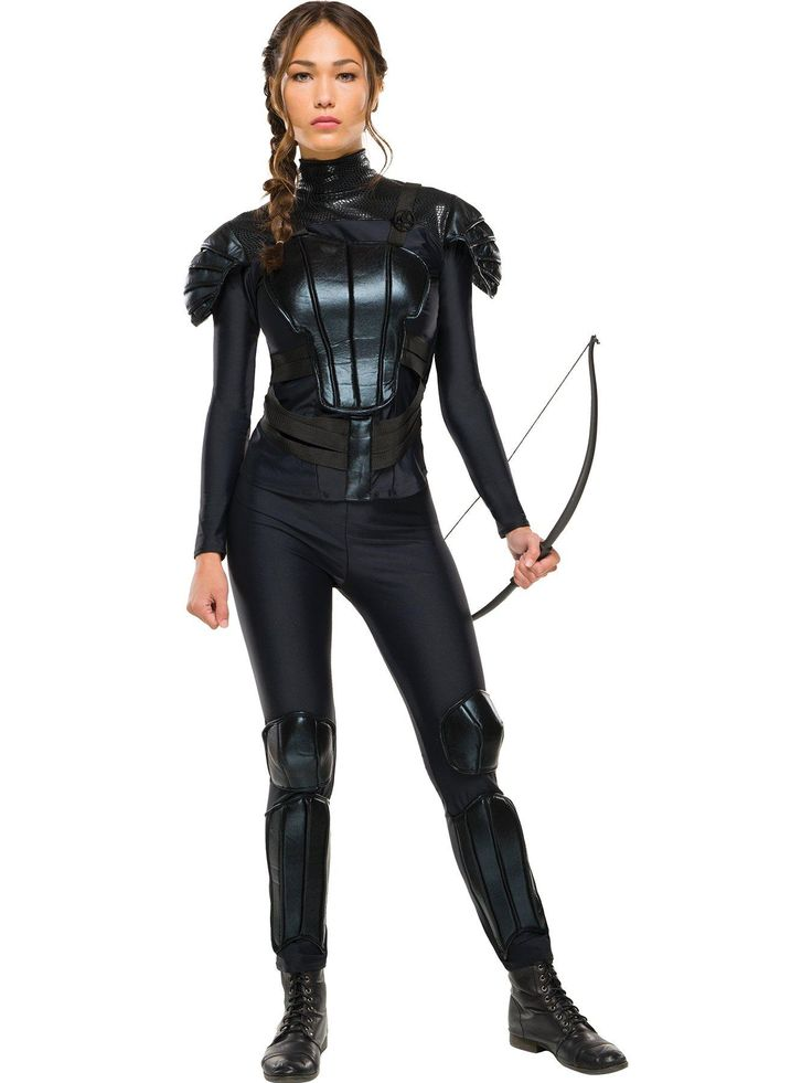 """Be ready to bravely face adversary in this Katniss """"Rebel"""" costume from The Hunger Games. It includes a black shirt with attached armour decoration, and black trousers with attached knee pads and shin guards. This costume also includes a Mockingjay pin. Available in sizes 6-8, 8-10, 12-14, and 14-16."""