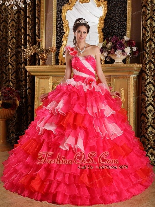Beautiful Red Quinceanera Dress One Shoulder Organza Ruffles and Beading Quinceanera Dress Ball Gown- $219.49 http://www.fashionos.com This quinceanera dress is incredible.This dress is strapless with large rosettes streaming over the shoulder. Ruching works through the bust and bodice.This gown has a drop waist with glittering stones and a ruffle detail. The skirt has tiers of ruffles with contrasting fabric. And the multicolor make the dress more charming.