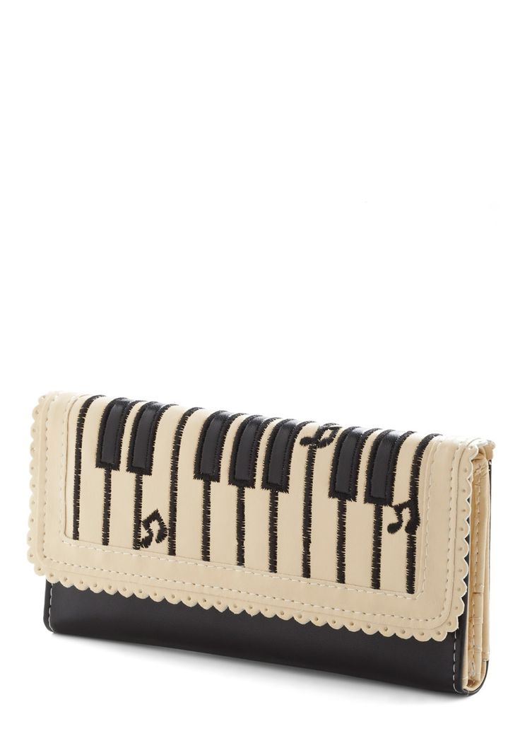 "Key Change Wallet...""If you're a music lover or a fan of quirky fashion, then this vegan faux leather wallet will really strike a chord! Its keyboard-embroidered flap conceals plentiful compartments for your cards and bills, as well as a zip-shut pouch for change. Tuck this cream-and-black wallet in your ivory purse, don a classic shift, and you'll be singing a happy tune!"""