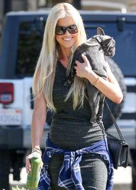 Flip or Flop's Christina El Moussa picks up a green juice while giving her dog, Cash, a lift. - Splash News Online