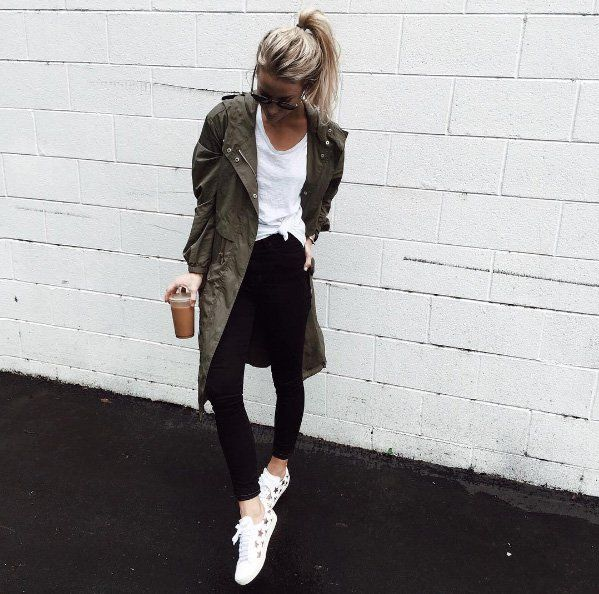 An olive parka paired with a basic tee, slim black jeans, and star-print sneakers.