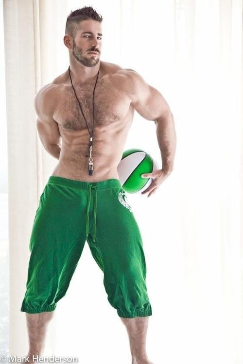 Shirtless hunk with hairy chest wearing green knee high sweat pants