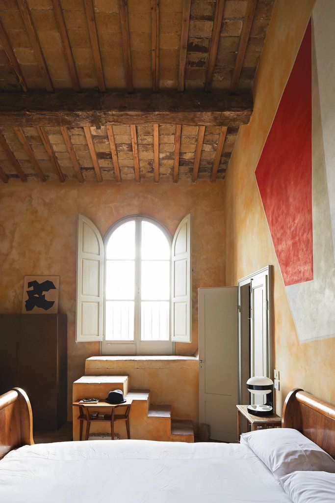 A 1950s Kartell lamp by Joe Colombo contrasts with 15th-century beams in one of the bedrooms.