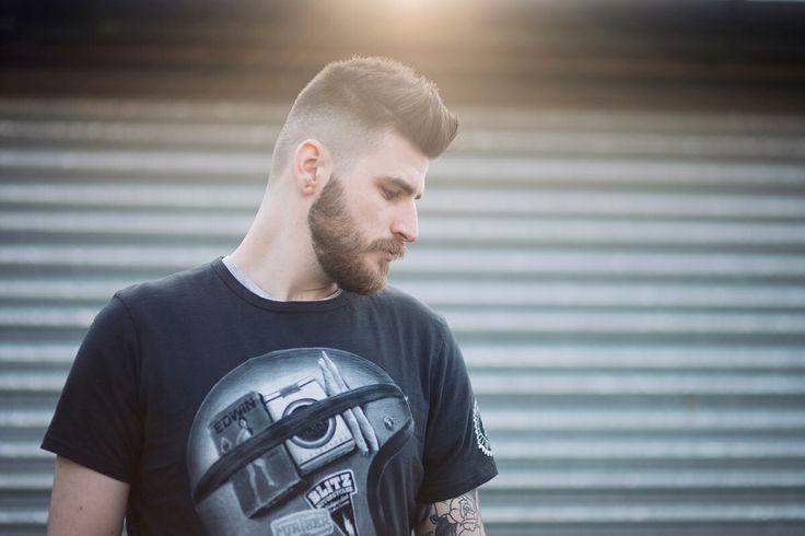 Male model with beard, naturally backlit, black tshirt, standing against shutterdoors.