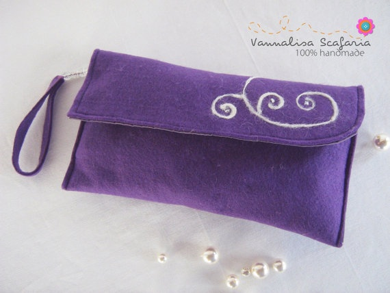 This purple clutch has needle felted swirls and additions of glass beads that make it a fairy handbag. Clutches are the fashion hit of the moment and,unlike you might think, they are practical and capacious.
