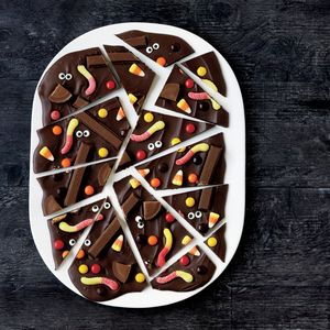 How to Make Haunted Chocolate Bark | MyRecipes   Decorate homemade chocolate bark with gummy worms, Kit Kat bars, candy corn, and more to make this festive treats.