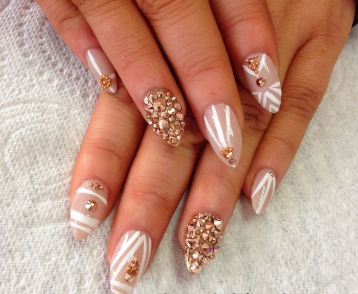 rose gold rhinestone nail decals, on beige pink colored sharp nails, decorated with white stripes