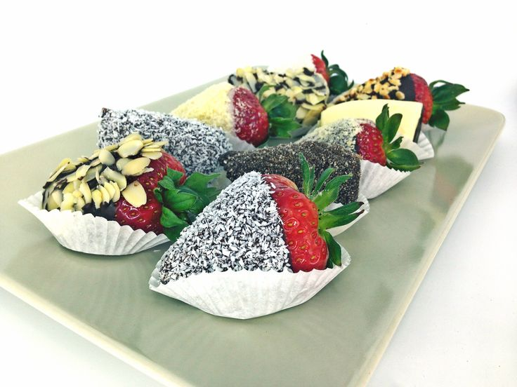 Sweet strawberries in white and dark chocolate with coconut and almonds