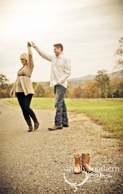 Country maternity picture: two-stepping parents in background, little boots in front.