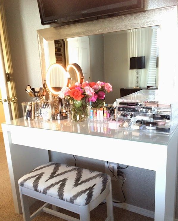 Fabulous dressing room features flatscreen TV over silver beveled mirror paired with Ikea Malm Dressing Table White topped and white and grey chevron vanity stool.