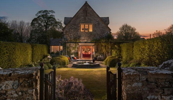 casas rurales baratas, villa de piedra con cerca de arbustos, jardín con césped y fuente