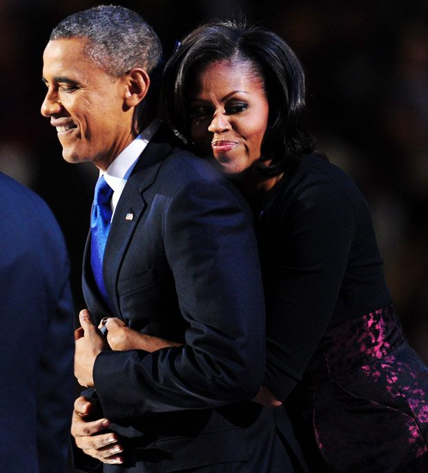 US President Barack Obama is embraced by First Lady Michelle Obama on stage after winning the 2012 US presidential election November 7, 2012 in Chicago, Illinois