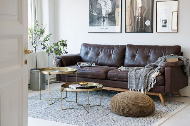 Gold coffee tables, ottoman and brown leather sofa.