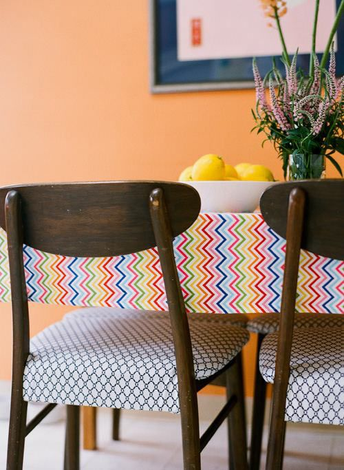 Orange kitchen wall, rainbow zigzag tablecloth, and thrift store chairs. It's the perfect mix of classic and fun!