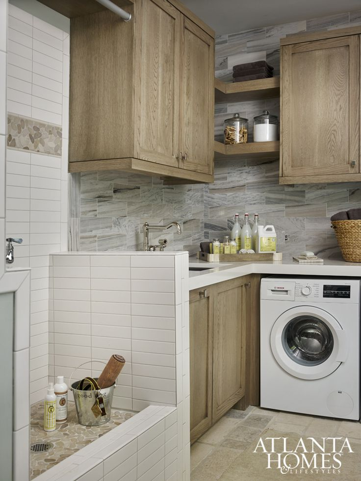 The laundry room contrasts with the mudroom's light-filled design scheme. French limestone flooring, also a smart choice for lakeside wear-and-tear, seamlessly ties both spaces together.