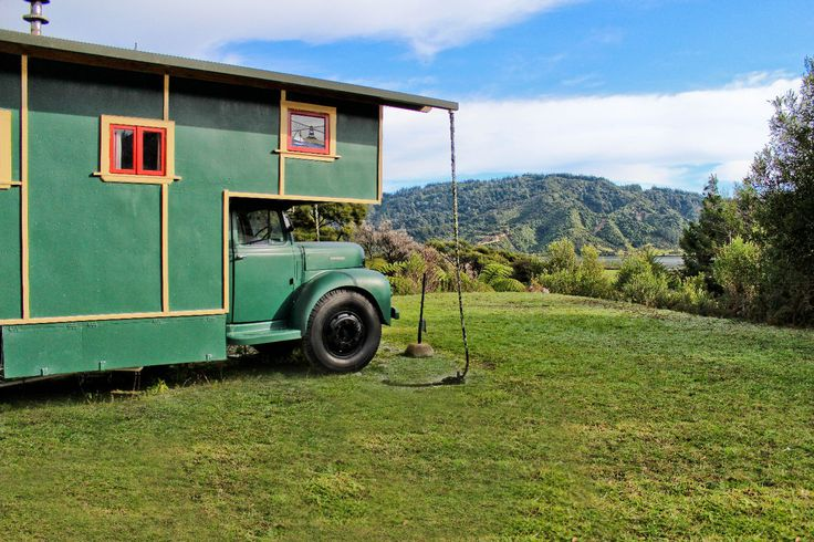 A New Zealand truck-turned house with stained glass windows, handcrafted kauri and oak timber interior, and a clawfoot outdoor bathtub.