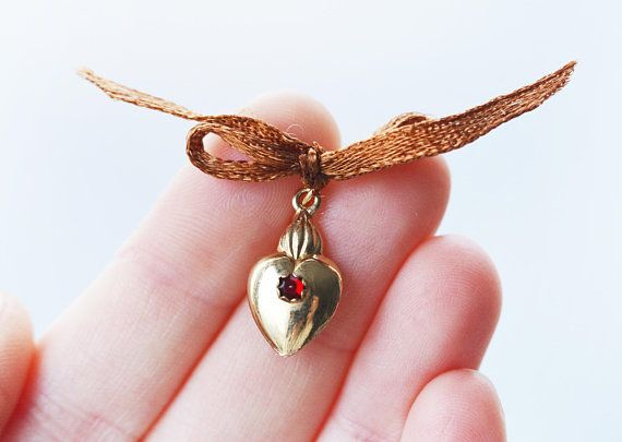 Red ruby set on an 18 k gold sacred heart - pendant or charm. Bow is just a gift bow, it can be taken off. Puffy heart, halmarked for 750 gold purity. Cute good luck charm! 10 mm wide 25 mm long with bale. Bale fits larger chains too. Hallmarks: 750 for 18carat gold, and what seems to be
